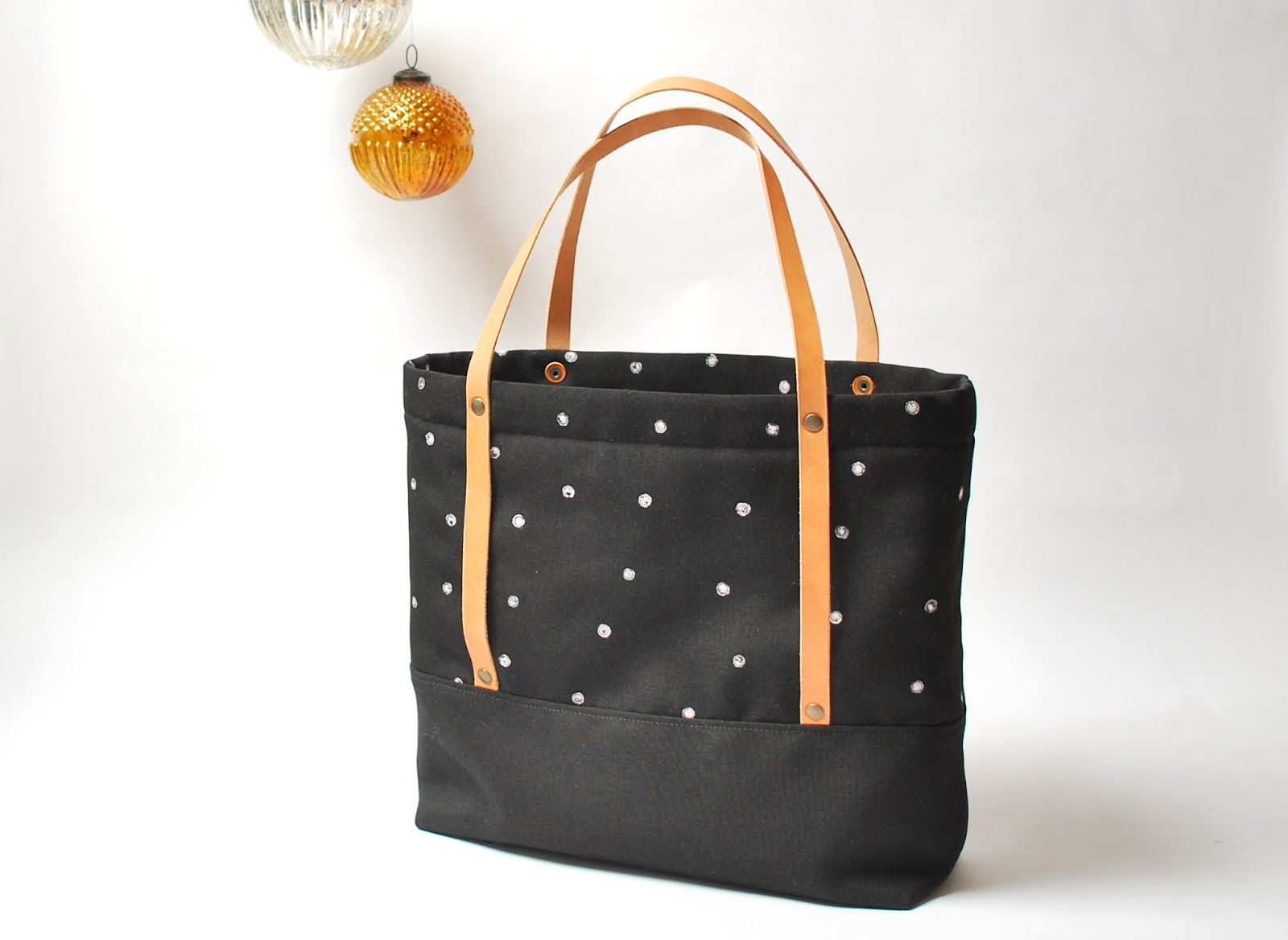 a black totebag with polkadots and leather straps