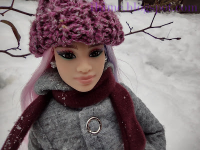 Closeup of Barbie with pink and purple hair in warm purple hat, standing in snow.