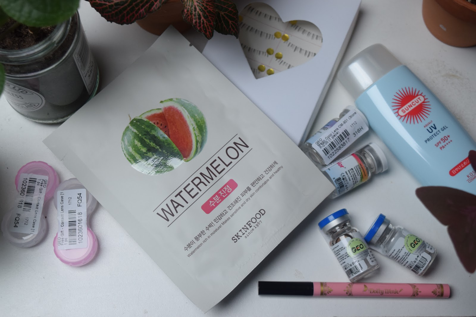 flatlay of Asian cosmetics and plants featuring Dolly Wink, Kosé, Skinfood, GEO
