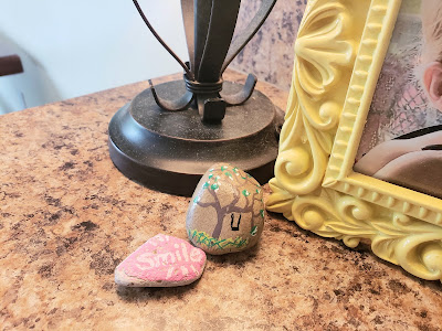 """We have an artist in the neighborhood who has gifted different homes with hand painted rocks. This week, I discovered this sweet tree swing on our mailbox. It joined the little smile little neighbor girls left on the mailbox in March when """"we were all in this together"""". I treasure both."""