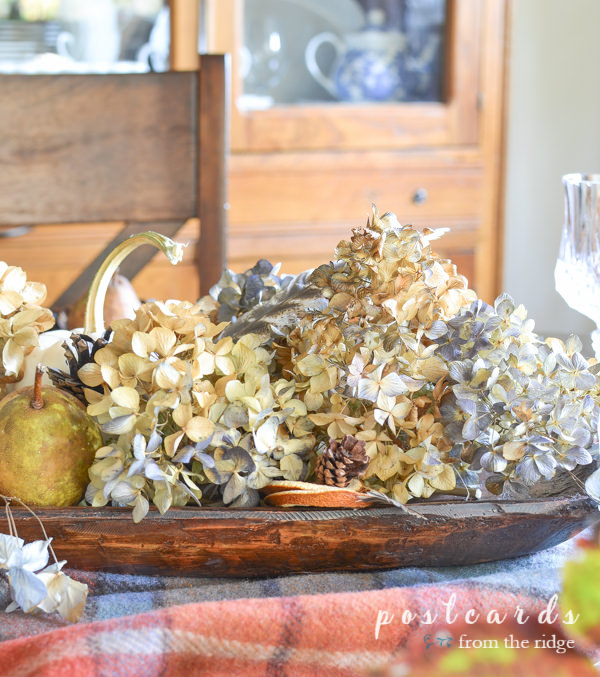 dried hydrangeas, white pumpkin, nuts, and acorns in a wood dough bowl