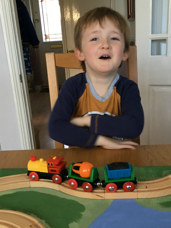Brio-Battery-operated-action-train-review-image-of-boy-with-big-smile-watching-train