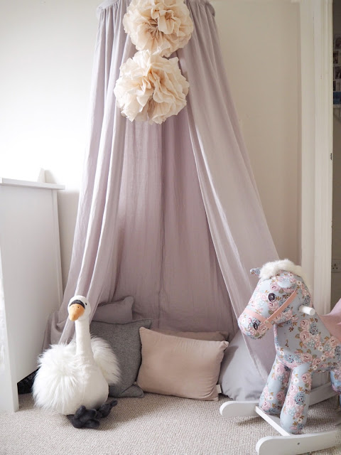 Nursery bedroom perfect for a baby girl toddler. Pink and swan ballet themed room with a sunburst mirror, feather lampshade, pom pom basket and liberty print rocking horse
