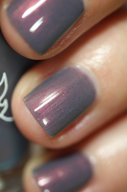 grey nail polish with copper shimmer swatched on white person's hands