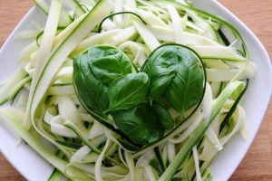 Spinach leaves forming a heart atop pale green-white pasta in a square white bowl