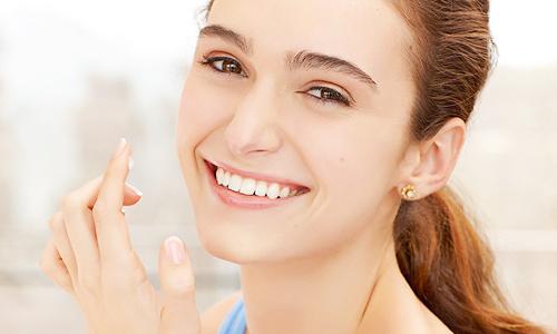 Chica joven aplicando crema hidratante