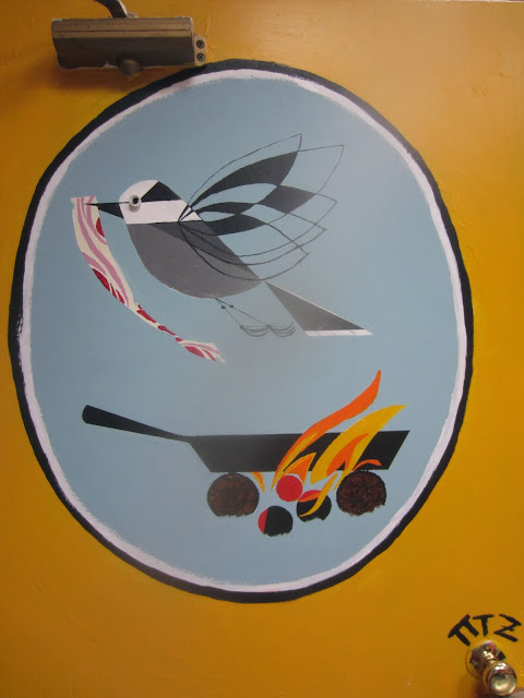 Rendition of Charley Harper's painting depicting a stylized bird flying off with bacon over a frying pan