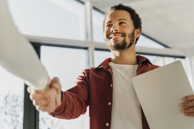 homem negro sorridente apertando a mão após conseguir um emprego