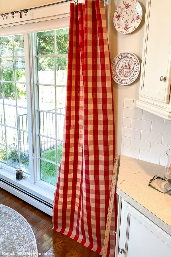 Hemming red buffalo check curtains by hanging them on the windows
