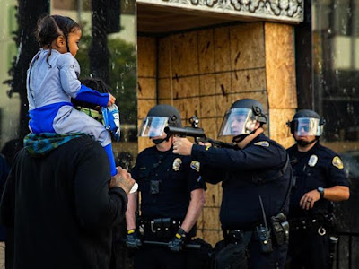 Three policemen in riot gear, one pointing a rubber bullet gun at a black girl riding on a man's shoulders