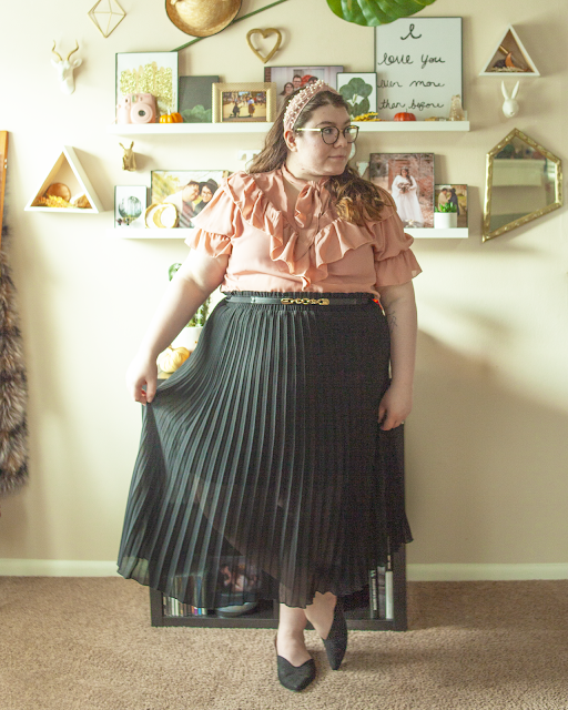 An outfit consisting of a pearl encrusted pink knotted headband, a pink short sleeve blouse with sleeve ruffles, and ruffles on the chest and a pussy bow neck tie, tucked into a black pleated midi skirt and black pointed toe slingback flats.
