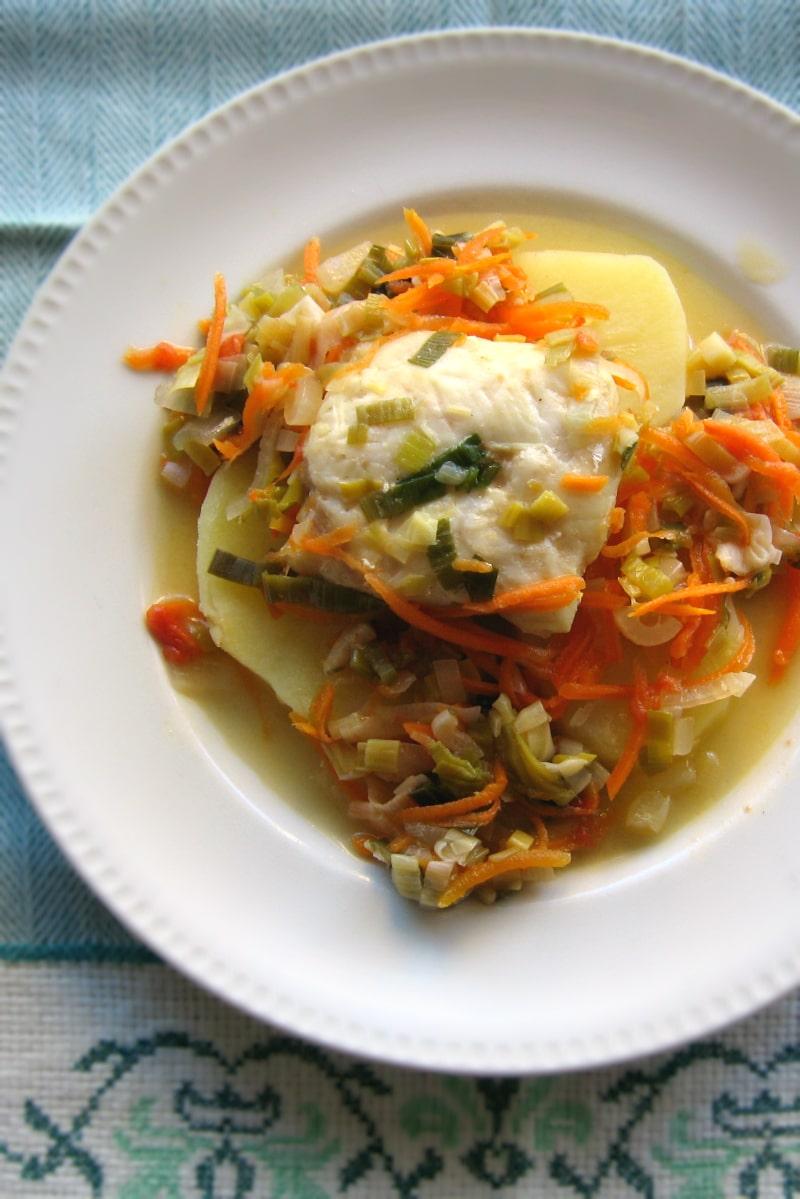 Porção de pescada sobre rodelas de batata cozida e mistura de legumes