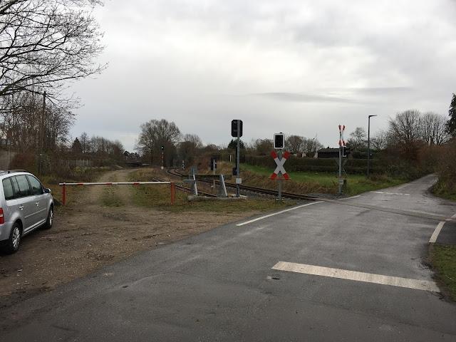 Hier geht der unbeschrankte Bahnübergang über das mit Beton oder Asphalt gefüllte Gleis und führt zwischen Schrebergärten weiter. Links steht ein silbergrauer Kombi, dann eine weiß-rote Schranke und ein Prellbock. Signale und Andreas-Kreuze sichern den Bahnübergang.