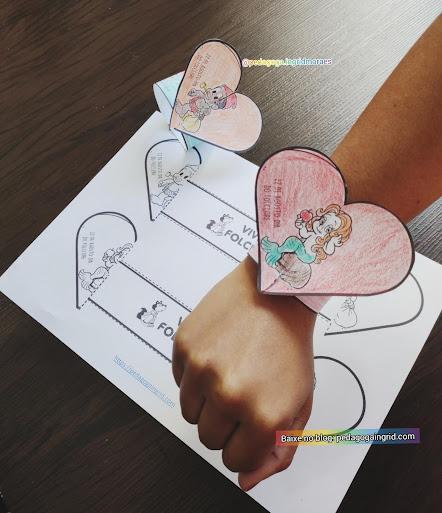 Imagem de uma mão com um bracelete de papel e com figura da iara e saci
