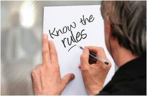 A man writing 'Know the rules' on the paper.