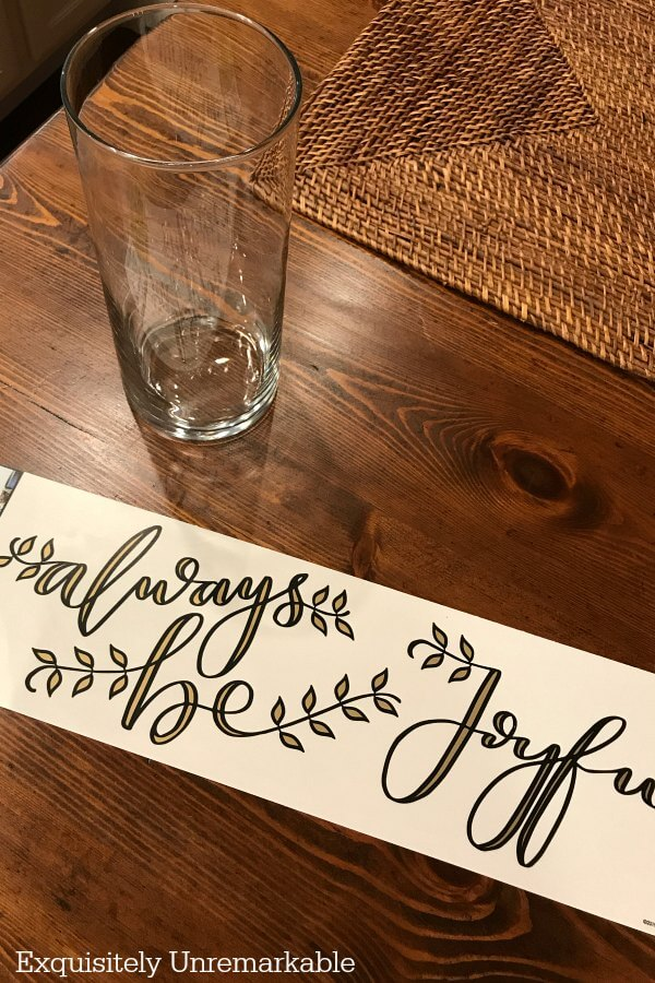 Be Joyful Always Wall Decal next to glass cylinder on table