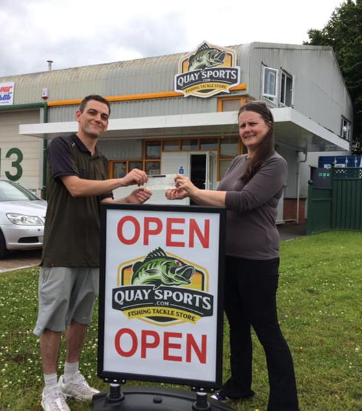 Quay Sports opening day donatation to Children's Hospice South West. Photo: Chris and Ruth outside the new store with cheque from new Quay Sports