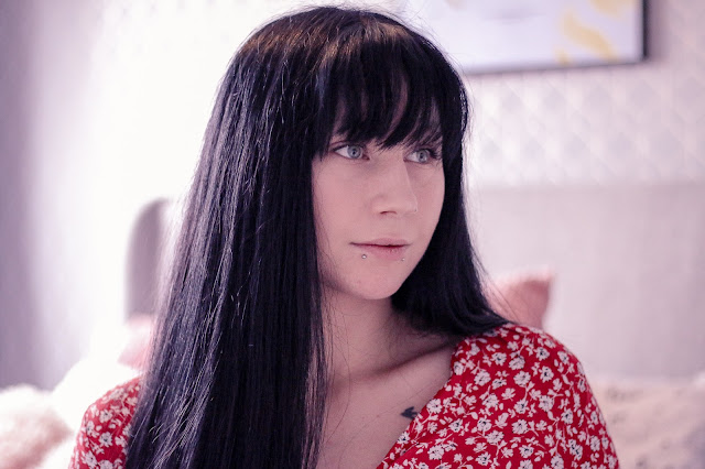 Medium close up of Jordanne (@ofaglasgowgirl) with long black hair looking off camera in a red flower dress