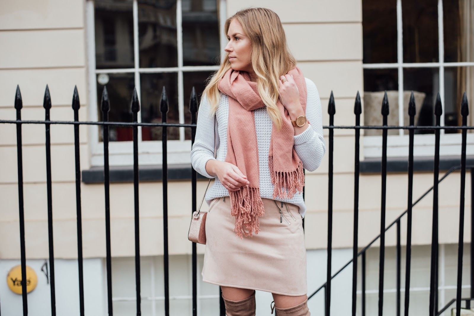 Rachel Emily Wearing Winter Pink Outfit and Looking Left infront of White Clifton Bristol Houses with Railings