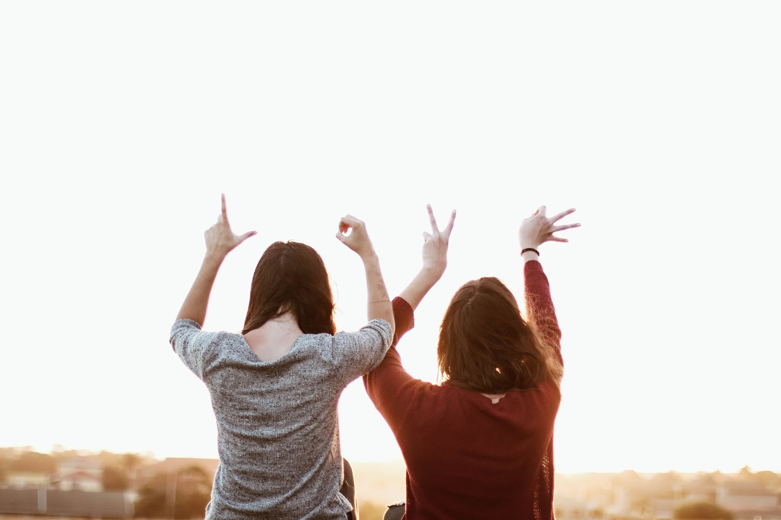 two women sitting while making love hand sign at daytime, love images