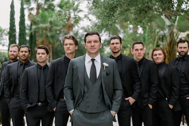 groom in grey suit with groomsmen in black suits