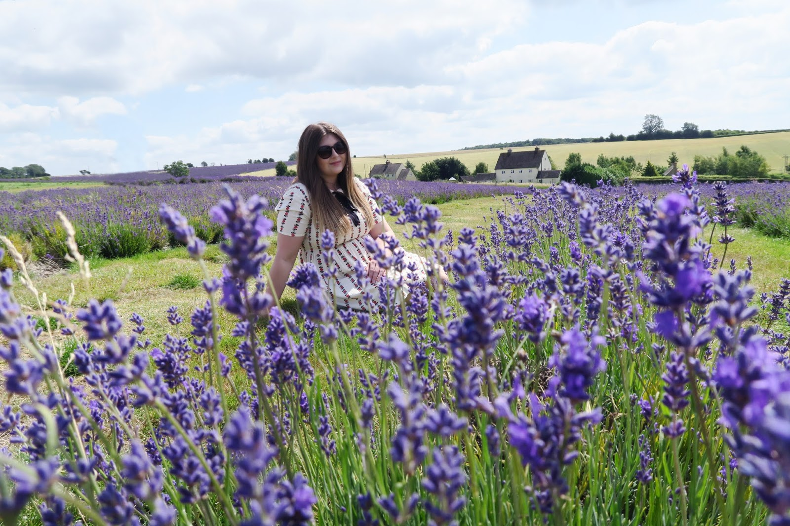Grace is sitting down between rows of lavender. Out of focus lavender can be seen in front of her and behind her farm houses can be seen