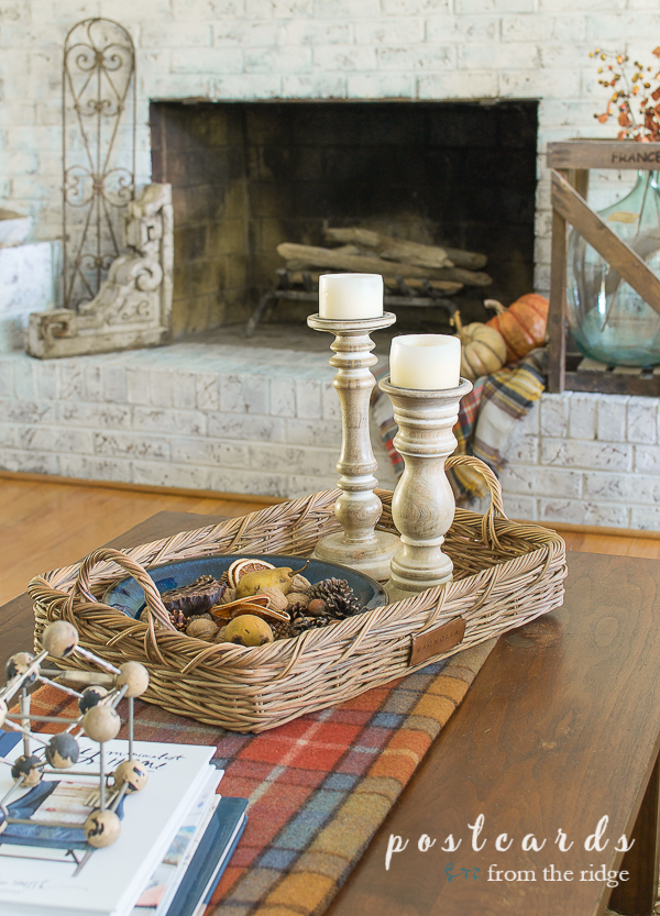 woven basket with wooden candlesticks on plaid blanket on wood coffee table