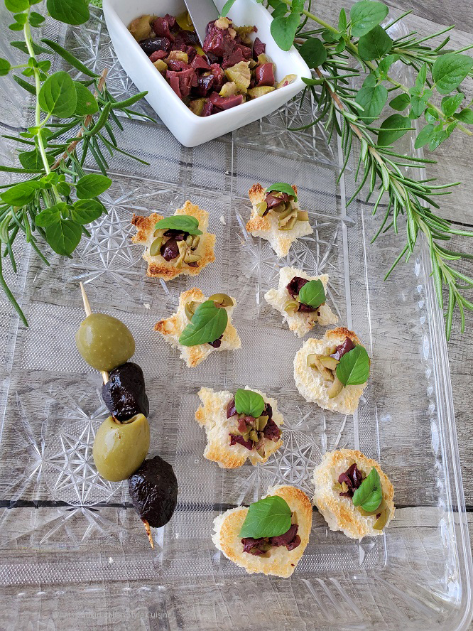 these are garlic toasted bread with olive tapenade on them there are also fresh herbs in the photo with an olive skewer