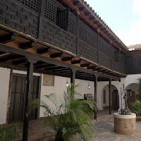 Santiago de Cuba, Innenhof der Casa de Diego Velázquez, Museo de Ambientew Histórico.  Blick in den gepflasterten Hof, umlaufender Balkon auf Holzstützen, auch nach innen ist der gesamte Balkon durch hölzerne Wände und Gitter verkleidet.