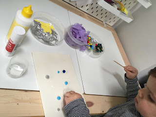 child gluing and sticking at craft table