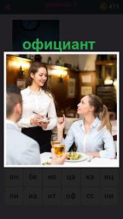 официант принимает заказ у посетителей сидящих за столиком