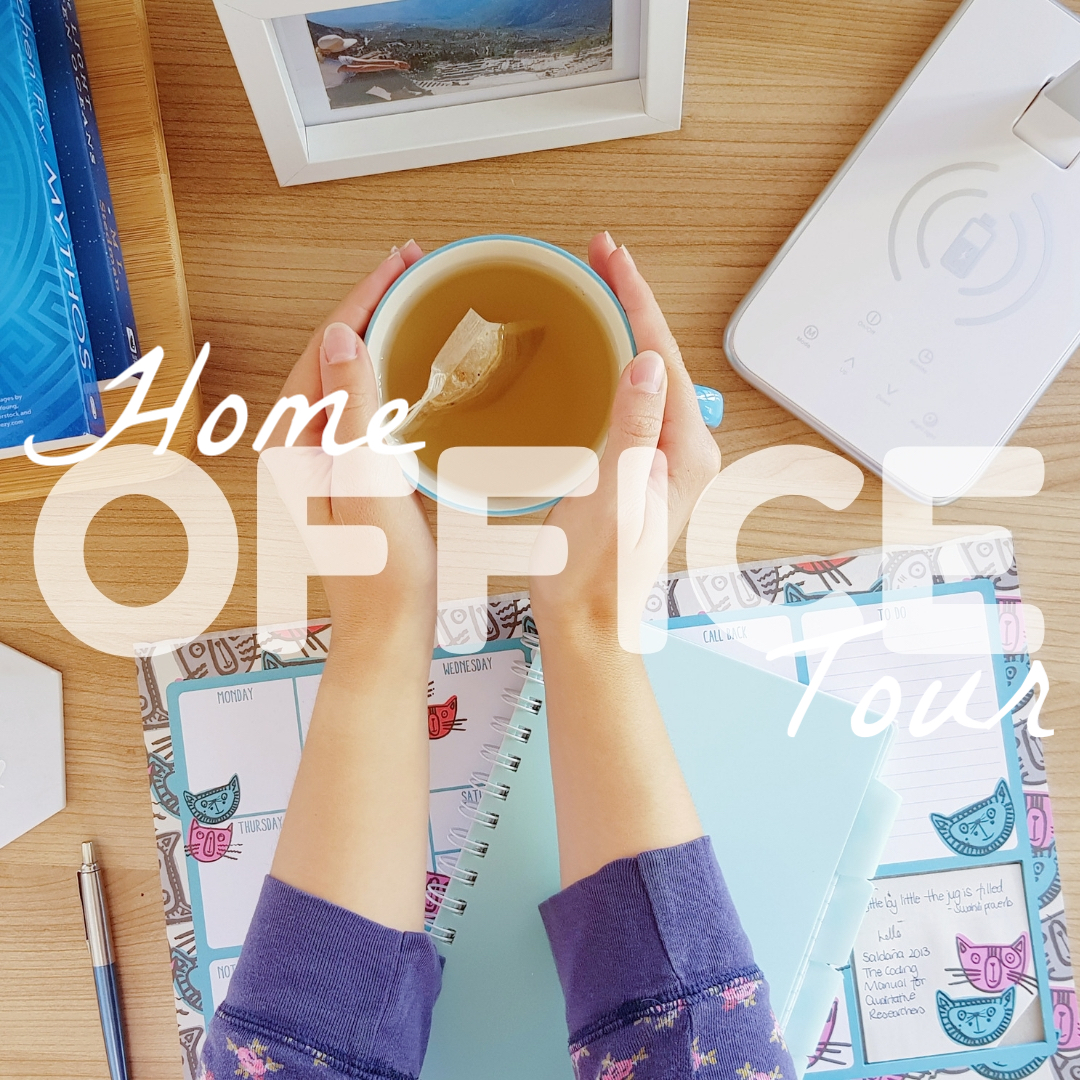 two hands holding a mug of tea surrounded by office equipment such as books, a lamp, pens, notebooks and a photo frame