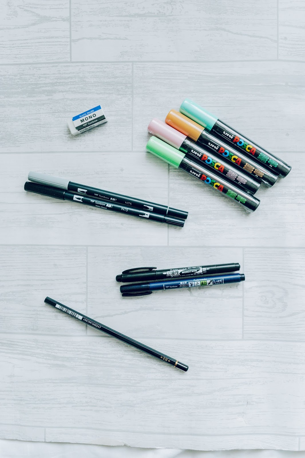 A selection of various colourful and black brush pens and paint pens.