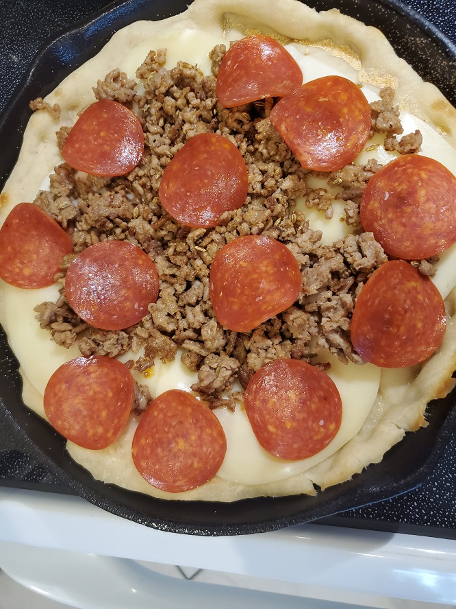 this is original deep dish ingredients on raw dough Chicago style pizza made on the grill in a cast iron skillets