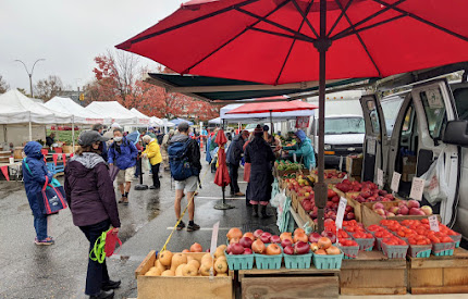 Masked crowd at farmers market in drizzle with tables of fruits and vegitables