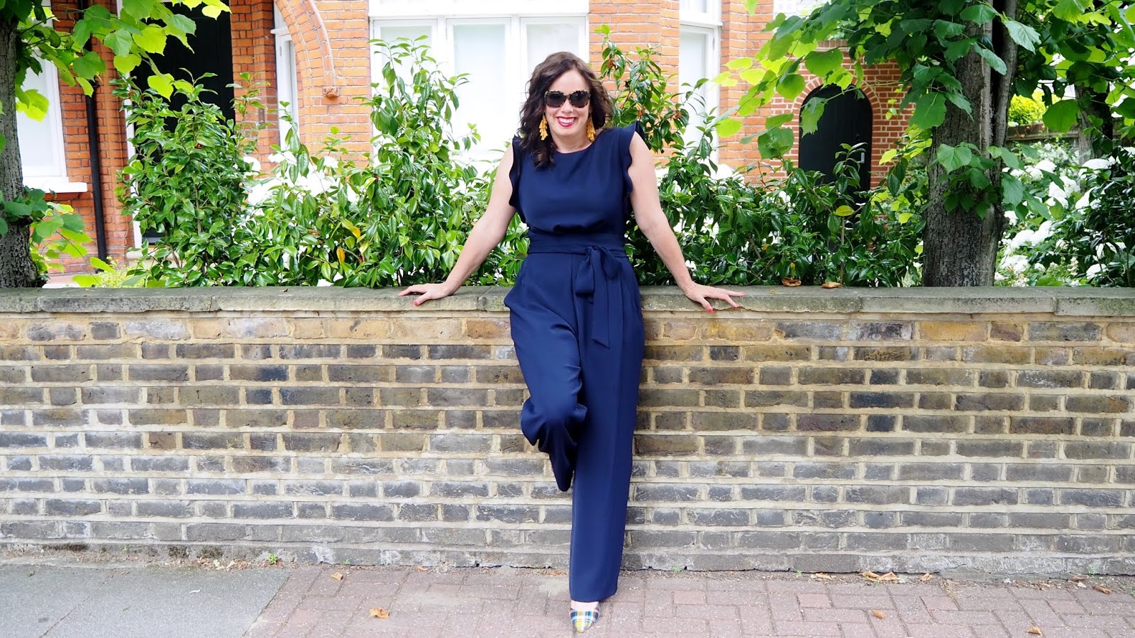 Navy jumpsuit with a tie waist and frilly sleeves