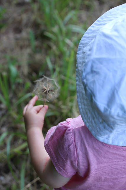 The view of a 1 year old from behind wearing a white hat and pink t-shirt and holding a dandilion clock. On the inside of her elbow a patch of eczema is visible.