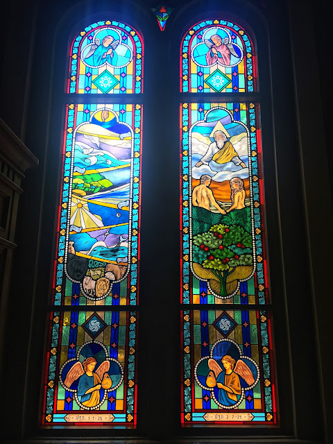 stained glass windows depicting the creation and adam and eve at bangkok's assumption cathedral