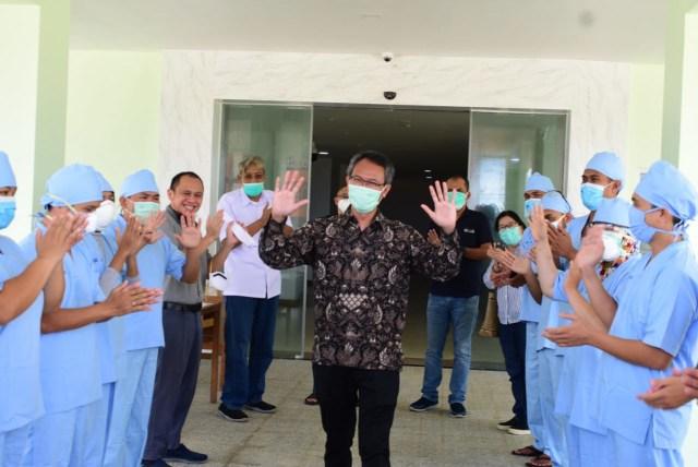 Pasien COVID-19 asal Sanggau yang sembuh diantar oleh para perawat dan Bupati Sintang, saat keluar dari ruang perawatan.