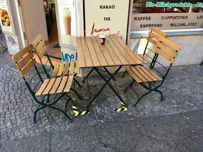 Vor dem Café: Tisch und Stühle mit auf den Boden aufgeklebten Markierungen