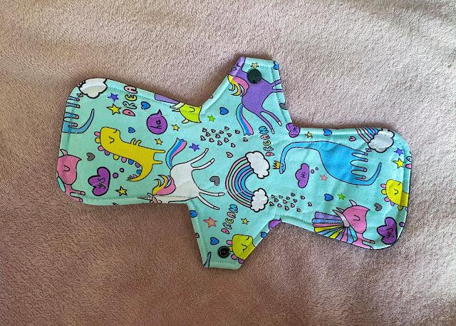 A fun long cloth sanitary pad with dinosaurs, unicorns and rainbow print