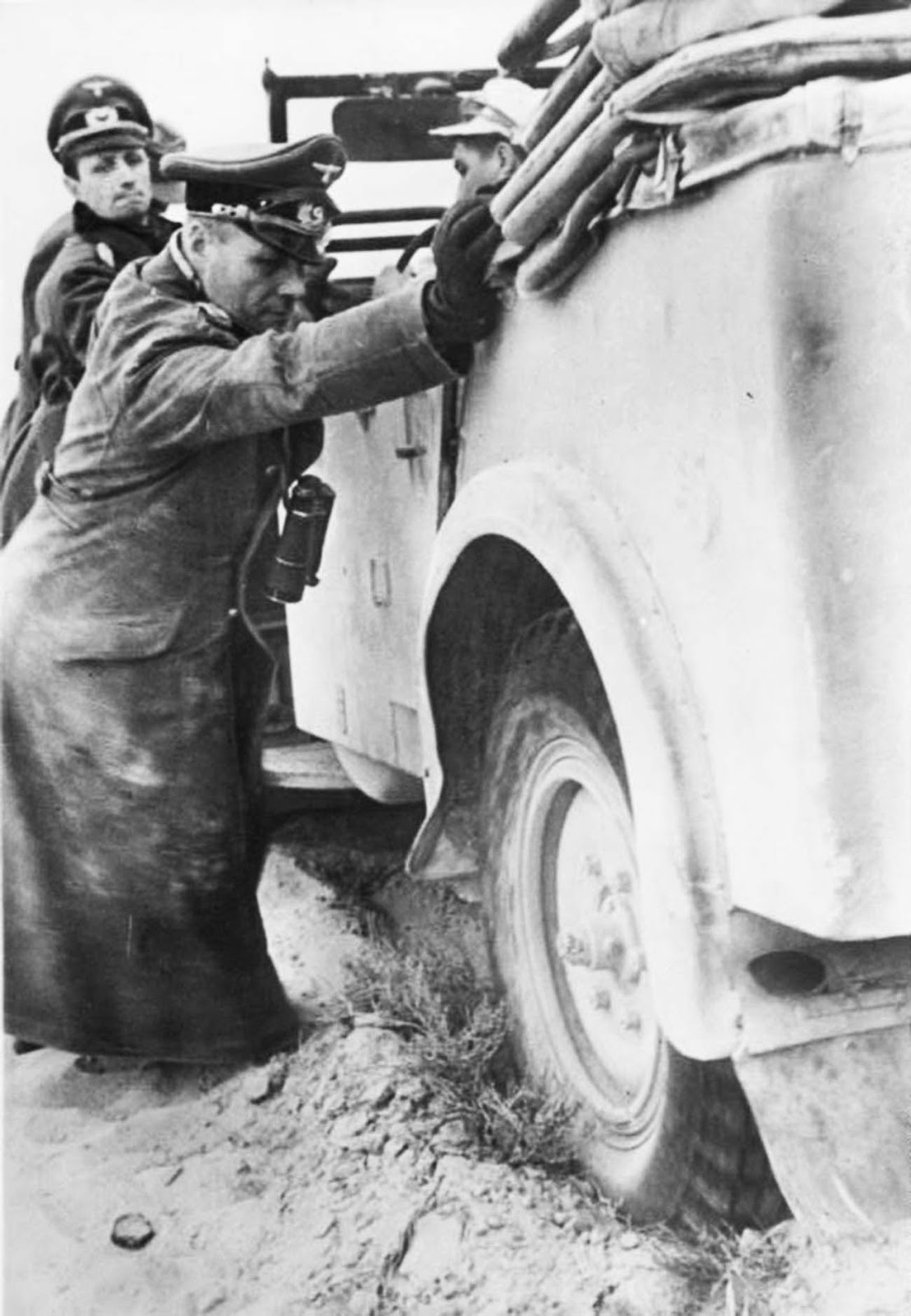 Erwin Rommel helps to push his stuck staff car somewhere in Northern Africa, January 1941.