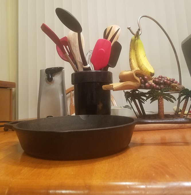 This is a cast iron skillet with a can opener in the background and utensils for cooking. Also some bananas