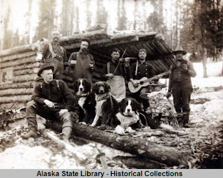 Six men and three dogs in front of a log cabin. One of the men has a guitar and one has a fiddle.