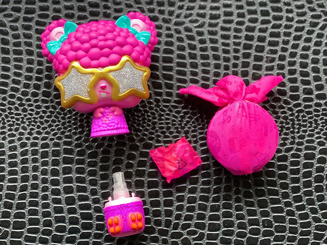 The brush separates to reveal a spray bottle and includes a pop surprise parcel and little bag with clips and bands in