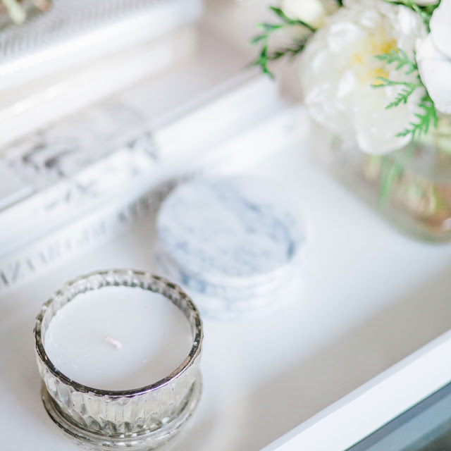 white lacquer tray with mercury glass lidded candle and marble coasters