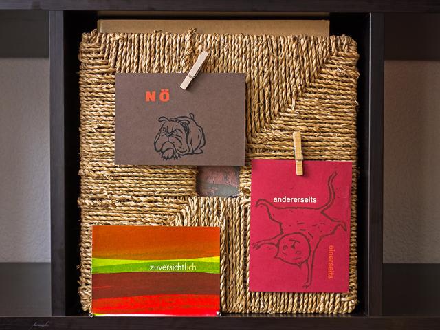 Eine Kiste aus Seegras, daran befestigt drei Kunstpostkarten von Cornelia Kurtz