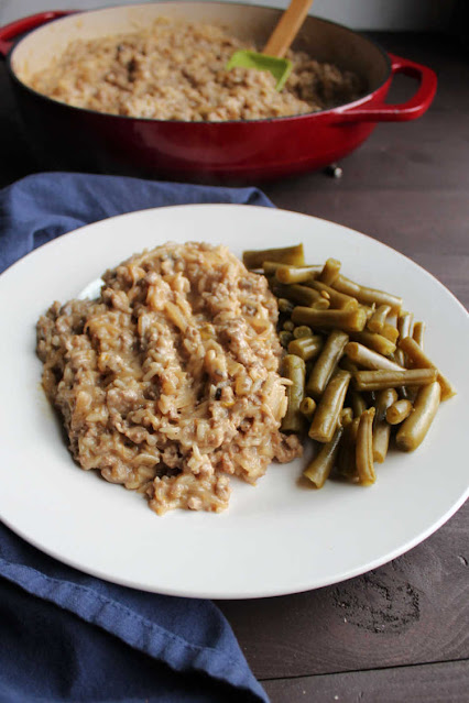 serving of creamy ground pork and rice in front of skillet of remaining dinner