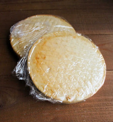two round white cake layers wrapped in plastic wrap