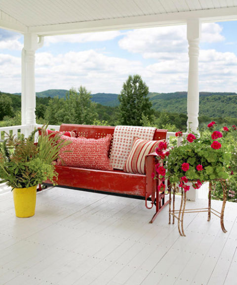 Red metal glider on a porch overlooking the mountains. Swoon!